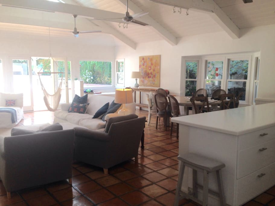 Spacious garden great room with large round wooden  dining table and comfortable seating for 6