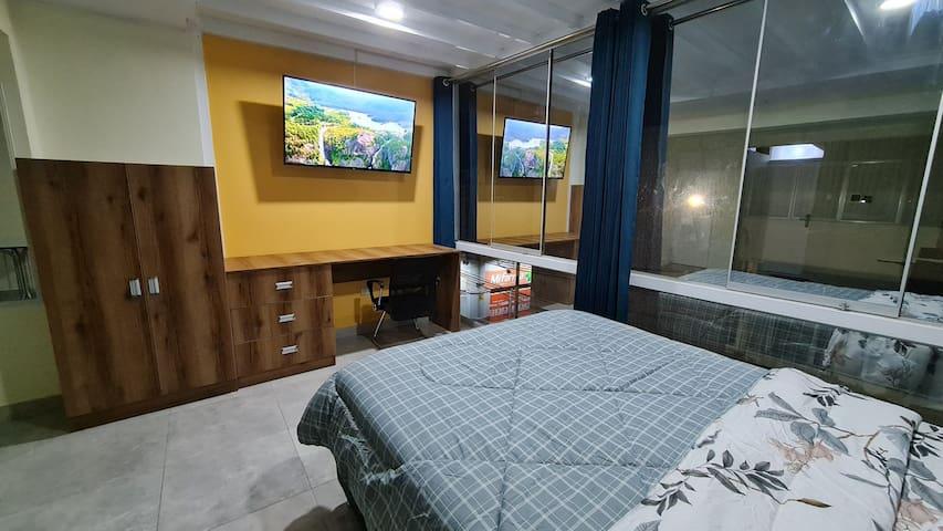 Habitación con cama Queen Size (2 plazas y media) y vista a la calle con ventana de Piso a Techo y cortina sol y sombra de 3 paños con dos ganchos metálicos para correrlas Apertura y cierre.