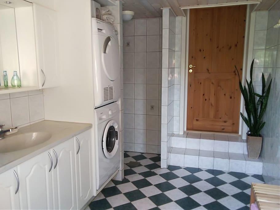 Stort badeværelse med vaskemaskine og tørretumbler.