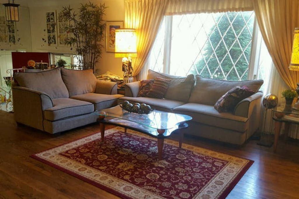 Living room has a sectional sofa and lots of natural light