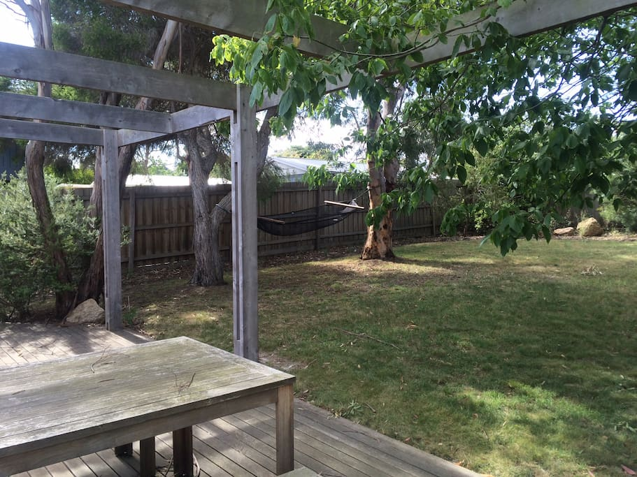 Large shady backyard with outdoor table, hammock and bbq