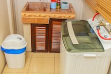 washing area with washing machine, soap powder.