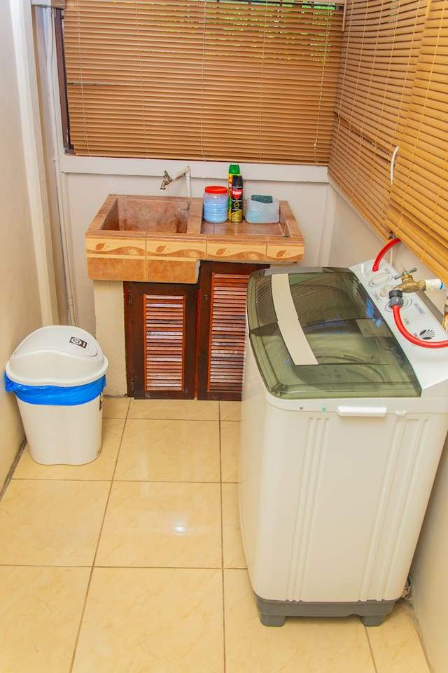 washing area with washing machine, soap powder.
