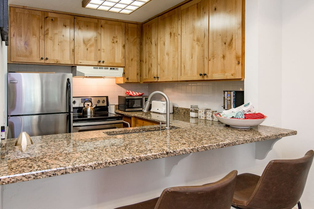 The kitchen includes stainless steel appliances and a breakfast bar with two stools.