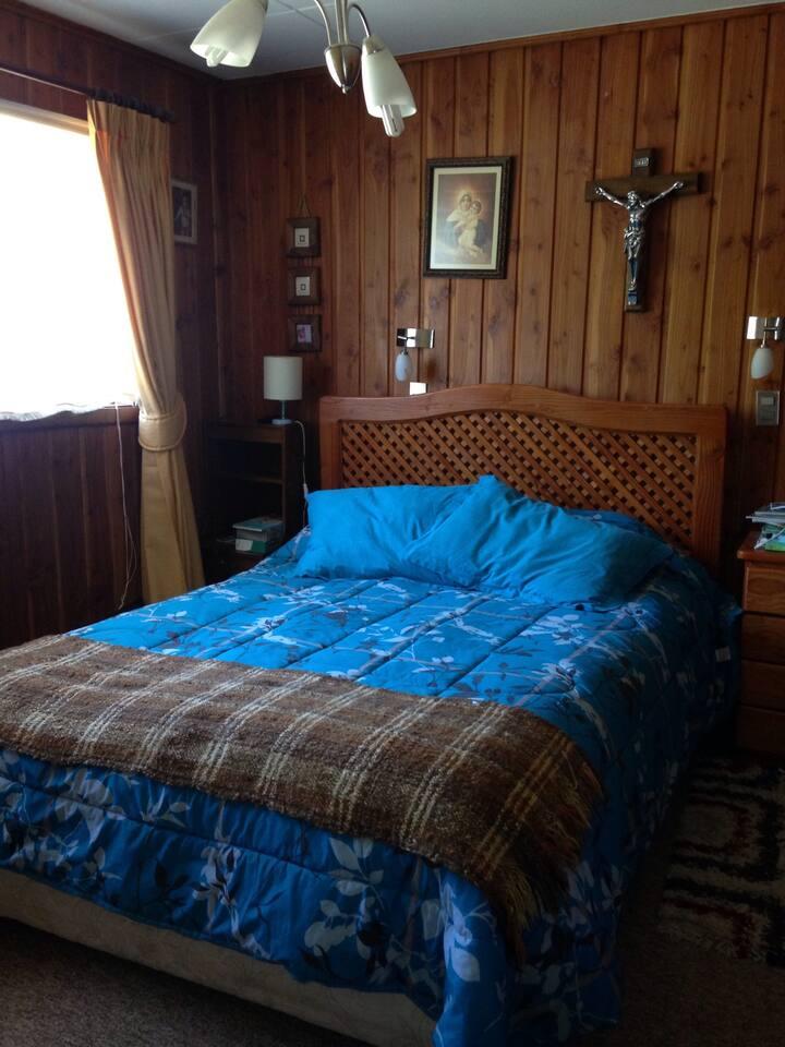 Dormitorio principal con cama matrimonial y TV