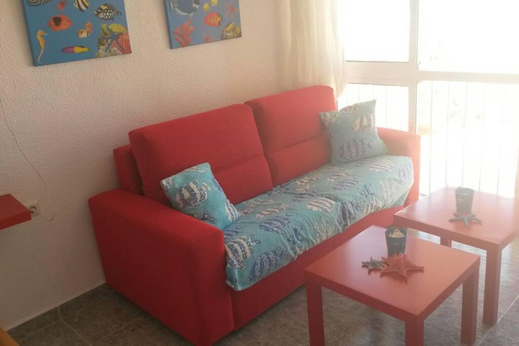 Sofa-cama al lado de  la gran ventana con vistas al mar