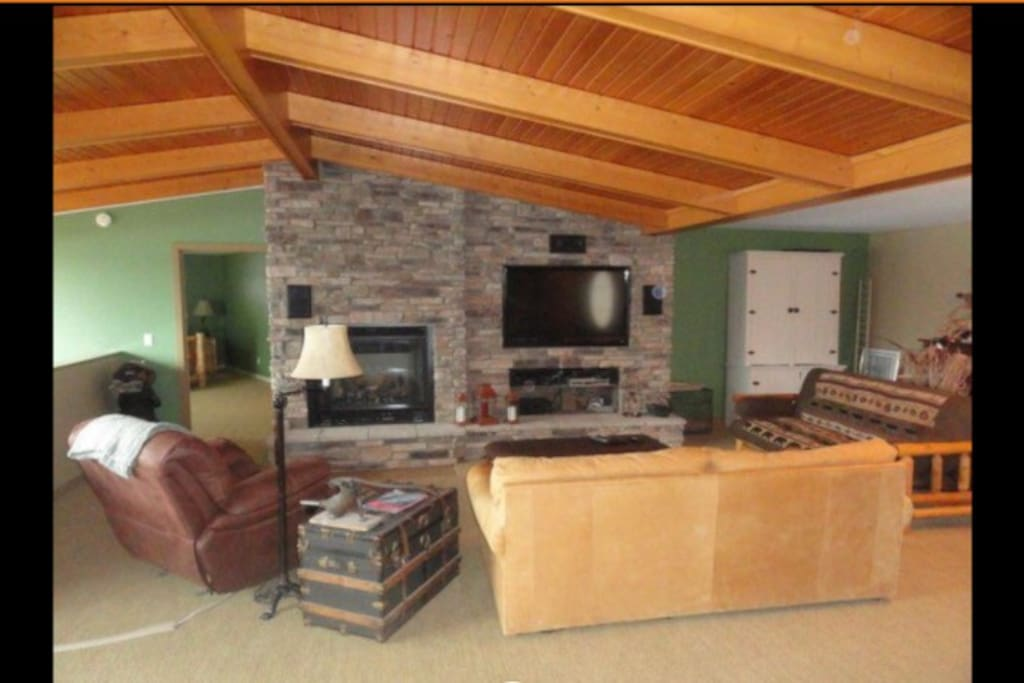 Family room features vaulted ceilings with beautiful stone and wood work.