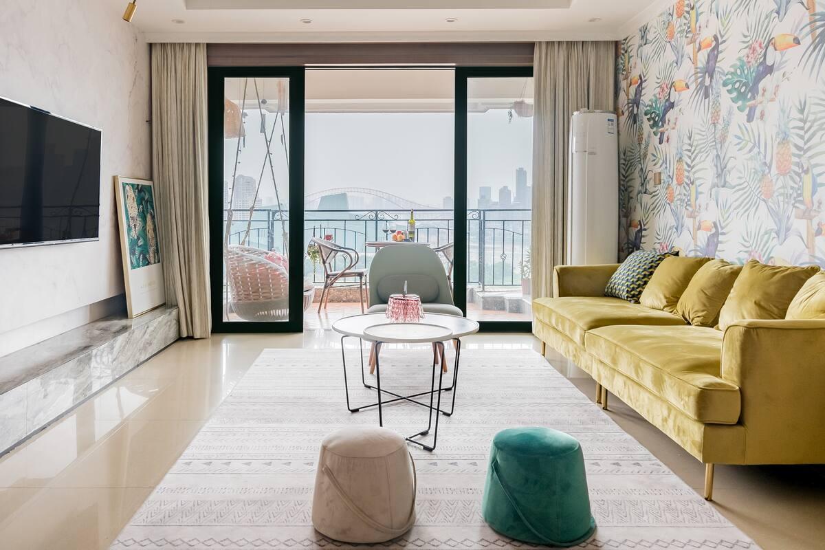 下榻色彩鲜明亮丽的时尚三居室,坐在阳台尽赏绚丽夺目的江景