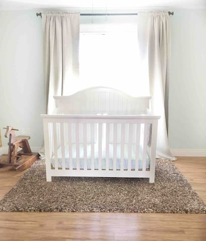 Full crib in kids room with room darkening curtains.