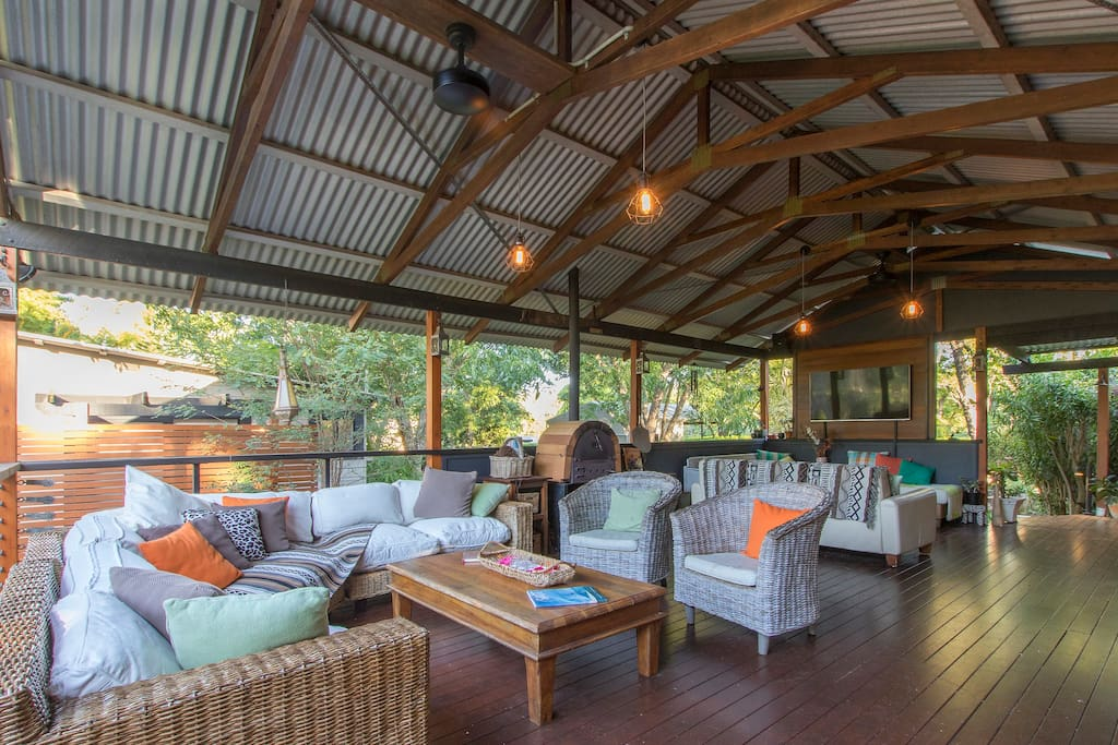 Covered outdoor area with comfy lounges, wood fired pizza oven and tv