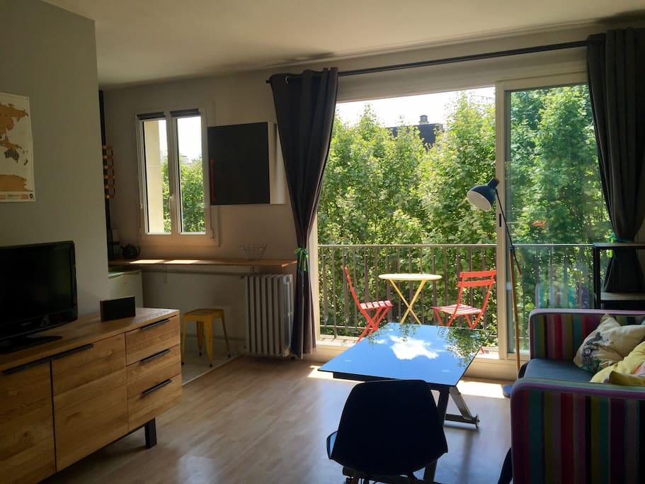 Coin salon avec grande baie vitrée coulissante donnant sur un balcon exposé plein Sud
