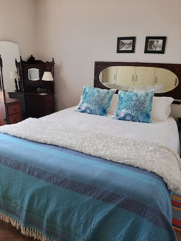 Main bedroom, with door leading onto deck. Furnished with antique furniture. Enjoy a comfortable sleep on high quality bedding. Ceiling fan keeps you cool in summer. Ample cupboard space.