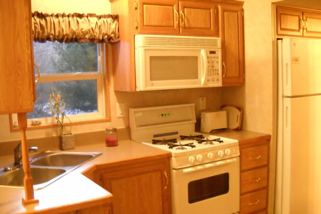 Kitchen with four burner gas stove, oven, microwave, toaster, coffee maker