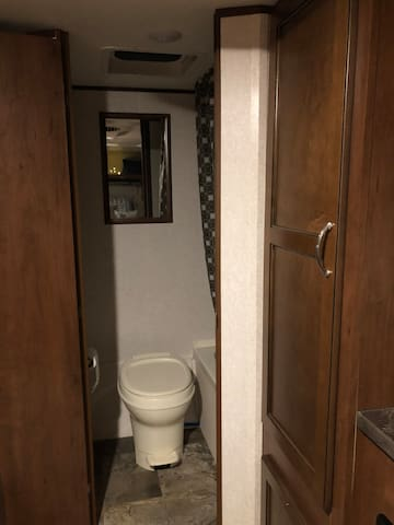 Standard RV toilet and tiny tub & shower, easy to use.