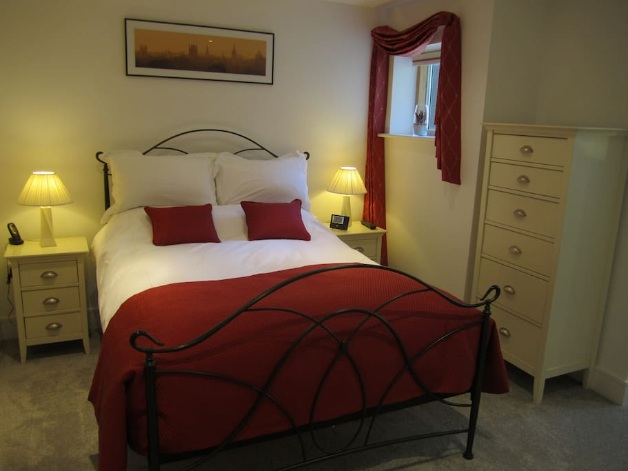 Spacious carpeted bedroom with goose down duvet and pillows.