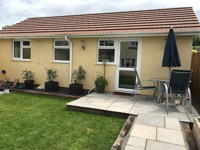 Pathway to annexe is level with a slight graded incline. Threshold at access door to the property. Sitting area outside on patio.