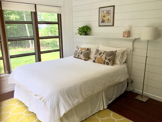 Queen sized bed with antique mantel headboard.