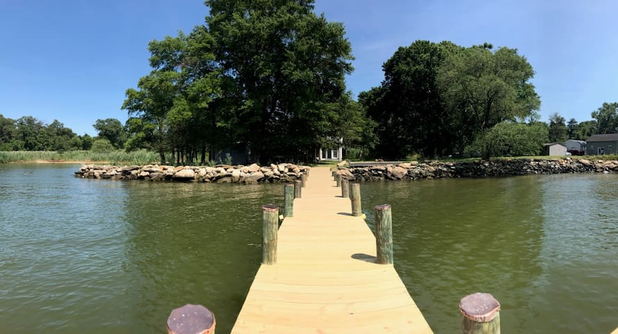 View of cottage from pier.  Gray shed on right is where visitors park.   Note variety of trees surrounding the property.  Sun or Shade, you will find both all day long.