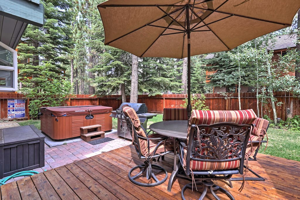 This home features a fenced-in yard with a hot tub, dining set and gas grill.