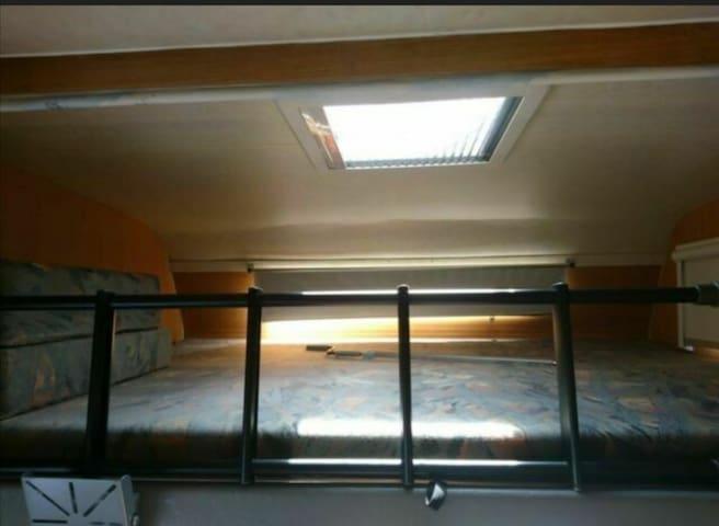 Blick von unten auf das Bett mit Leiter über der Fahrerkabine.