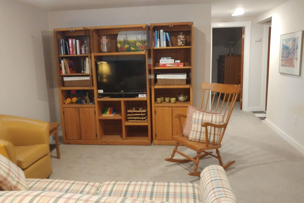 View from the dining area shows entertainment center.  The TV is equipped with a Chromecast device that allows you to cast accounts you have available on your phone, e.g. Netflix, Hulu, and Spotify, to the TV for streaming.  The hall to the bedroom and bathroom are on the right.
