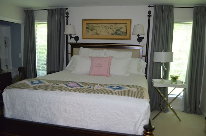 A comfy king bed with upholstered headboard, top quality mattress, and premium cotton sheets and cotton quilt. Wall-mounted lamps make nighttime reading enjoyable. Windows overlook private lawn and woods.