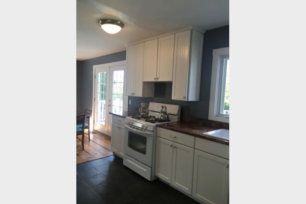 Newer kitchen with marble countertops and full sized fridge to the left out of this frame.