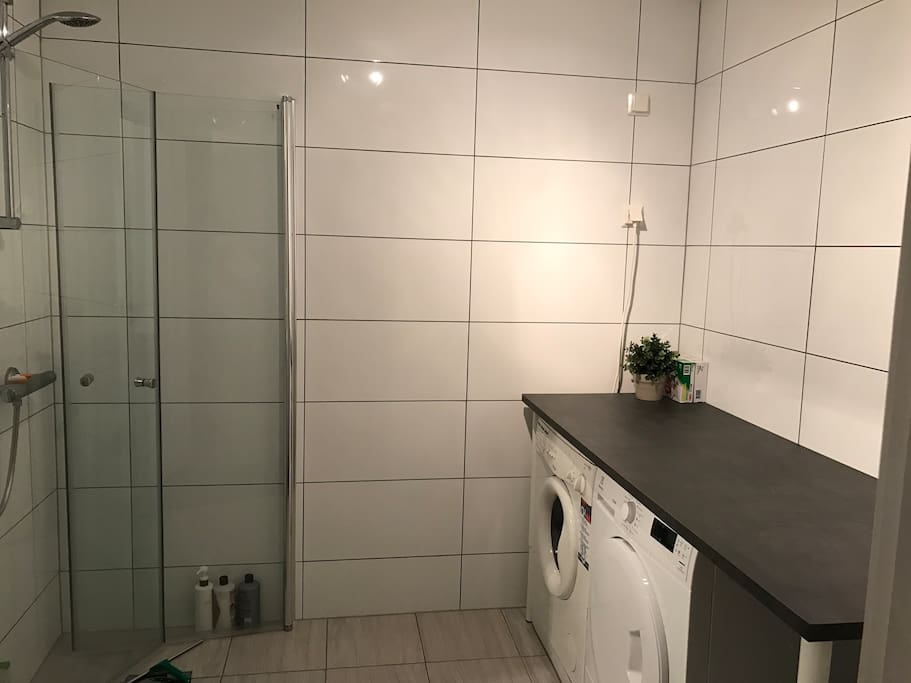 Bathroom with big shower, and also washing machine and dryer.