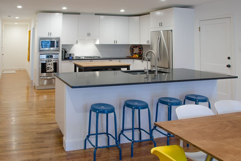 The fully updated kitchen has bar seating for 4, a center island great for food prep or storing your keys and wallets, and a huge honed granite sink island overlooking the dining and seating areas and out onto the deck outside