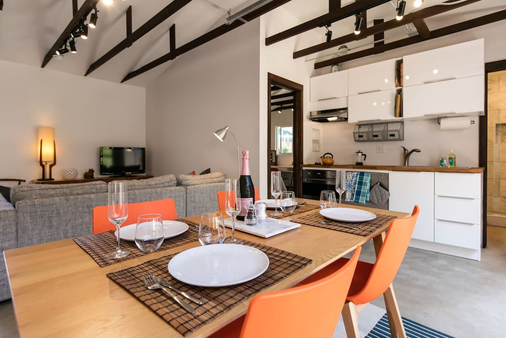 The dining area, living room and kitchenette are brightly lit from the large roll up door of the converted back house.