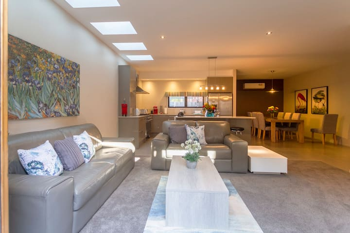 Living room with bifold doors fully opening to outdoor alfresco with outdoor additional dining setting.
