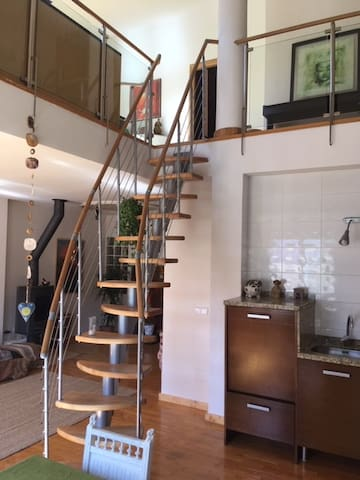 Open kitchen area with stairs to upstairs music space
