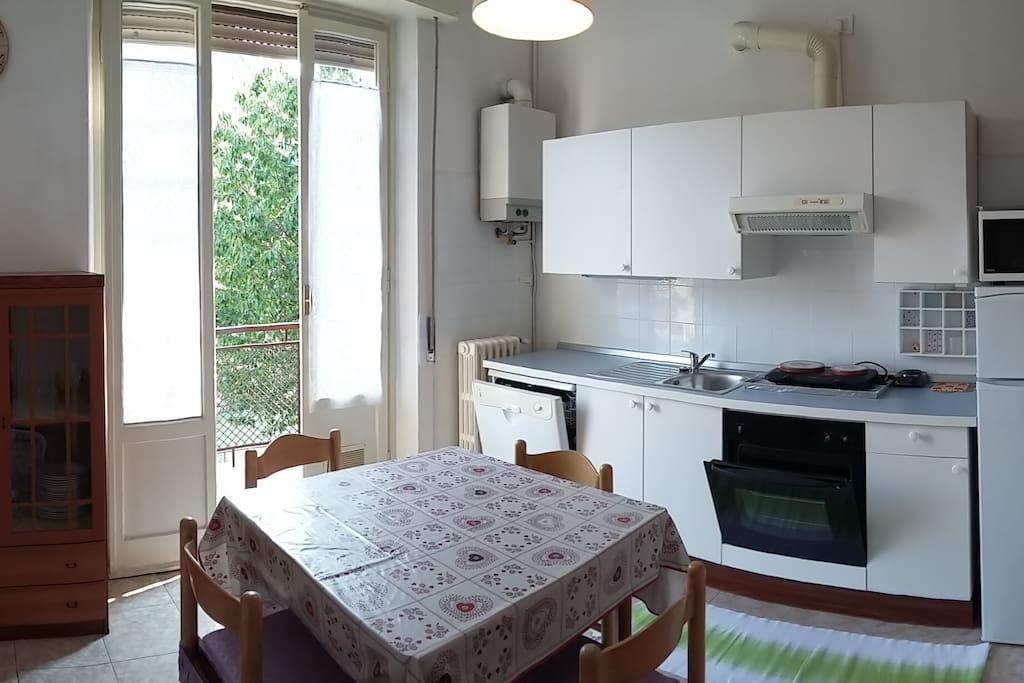 Cucina completa di stoviglie, pentole e elettrodomestici.
