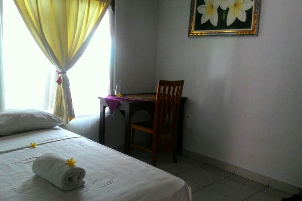 Comfortable Room with singgle bed, towel, and table