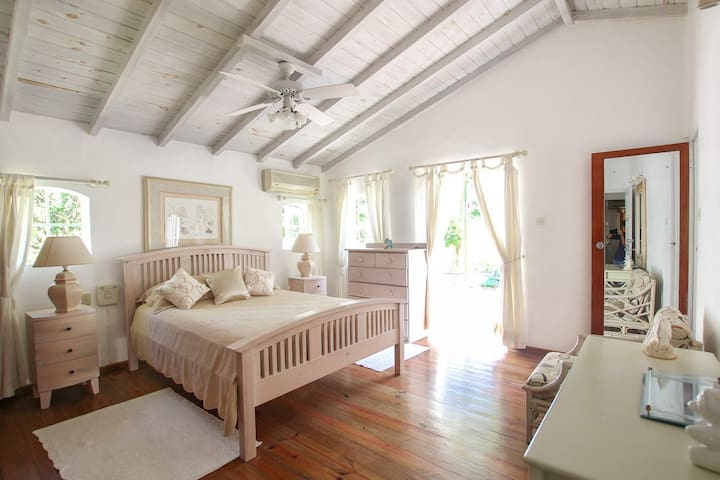 The master bedroom on the upper floor has french doors overlooking the entrance, air-conditioning and en suite