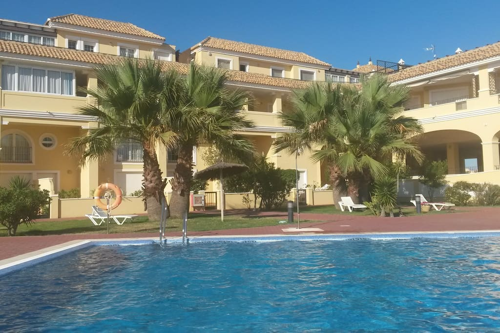 Fachada interior de pequeña urbanización con piscina y padel gratis