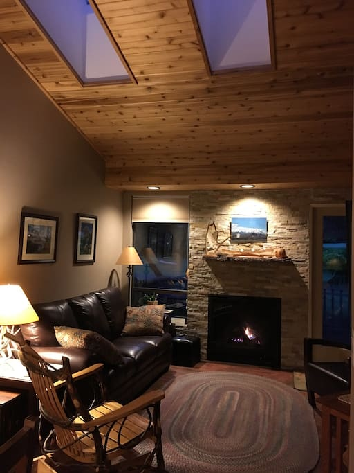 Vaulted cedar ceiling with sky lights and gas fire place in living room