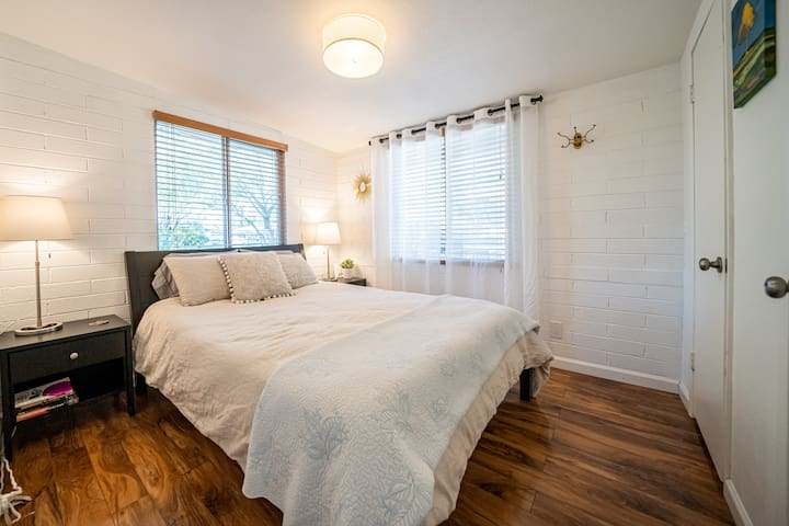 The second bedroom with a queen bed - cotton and linen bedding with lots of pillows, 2 large windows, hooks for your stuff and a large closet.