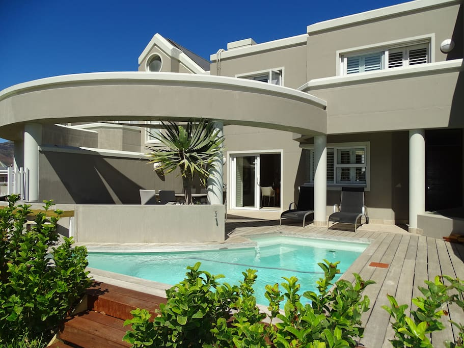 Outside of townhouse with shade covered dining area, sunloungers, BBQ and solarheated splashpool