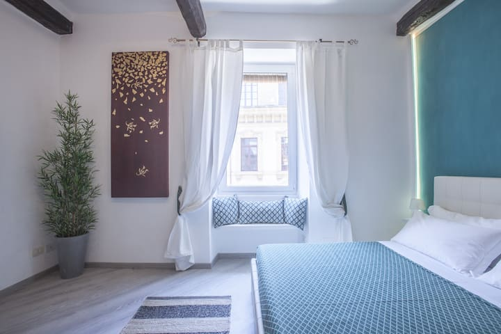 the bedroom with the large window overlooking the avenue of the Portico Di Ottavia
