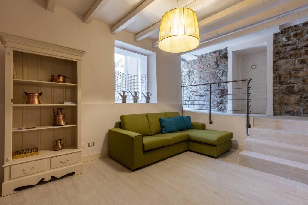 Luminoso e spazioso soggiorno con divano completo di penisola ideale per rilassarsi.