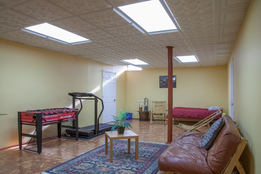 Large living room with Futon sofa/bed,  TV, Foosball table, treadmill, and spare bed