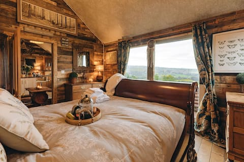 The Lodge at Caradoc. Hillside Retreats.  An offgrid rural log cabin with hot tub, fire pit  and decking area. With amazing views.