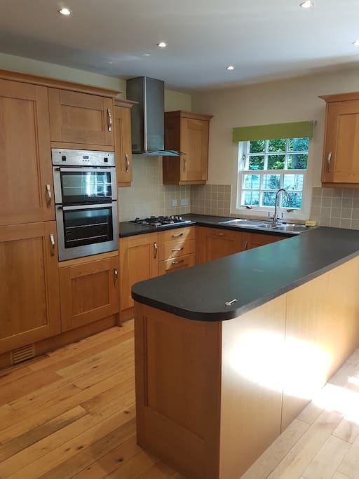 Large dining kitchen with oven, grill, hob, dishwasher, fridge freezer, washing machine and tumble dryer.