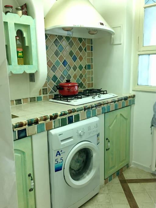地中海风格的小厨房,炊具、调理齐备。另有全自动洗衣机。