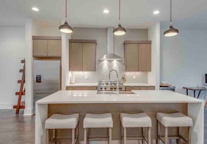 Chefs kitchen with high-end appliances and large waterfall quartz island with seating for four