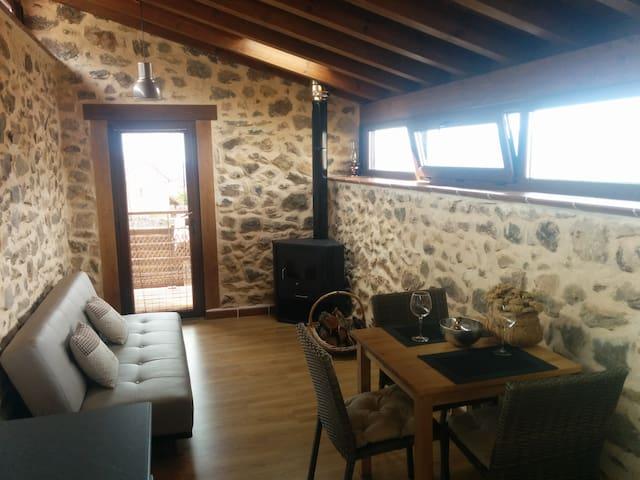 Planta superior: mesa, sillas, sofá cama, salida al balcón, estufa de leña