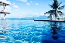 La piscine à débordement 20 mètres x 12 mètres avec son bain à remous et sa superbe vue sur mer