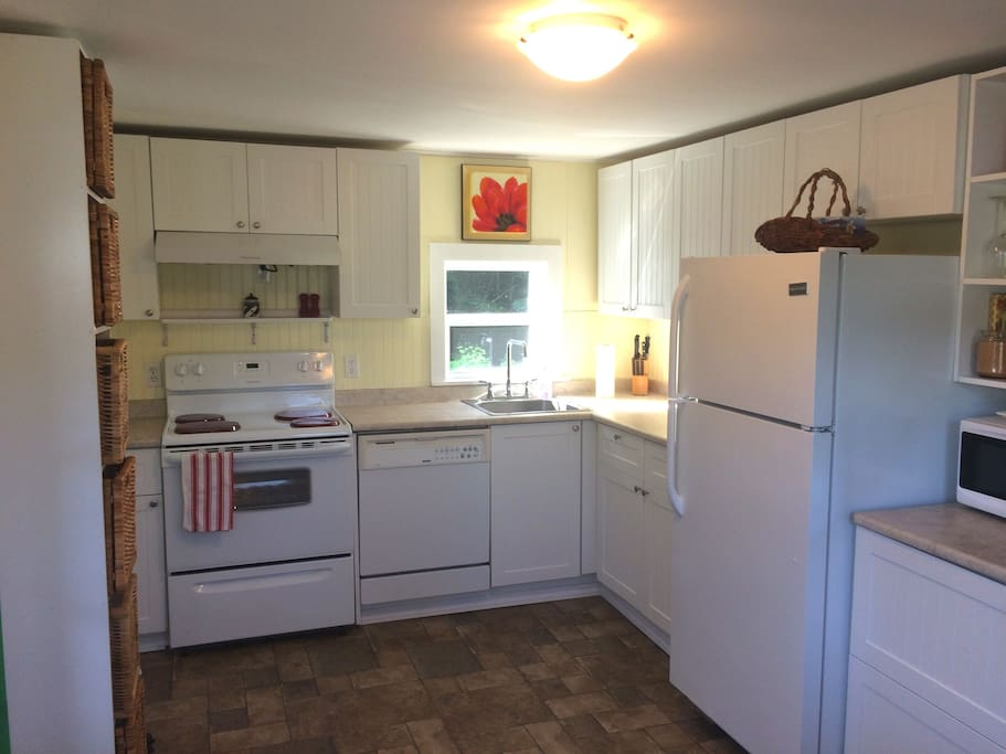 New Kitchen with all appliances and kitchenware.