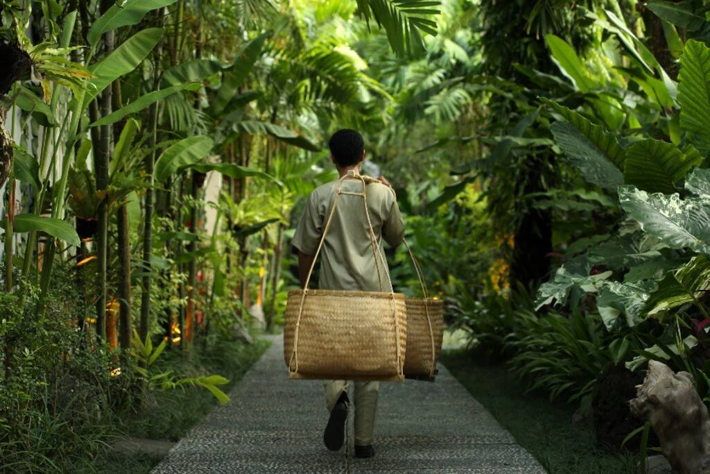 Personalised service: Housekeeper carrying amenities in an Indonesian vintage style.